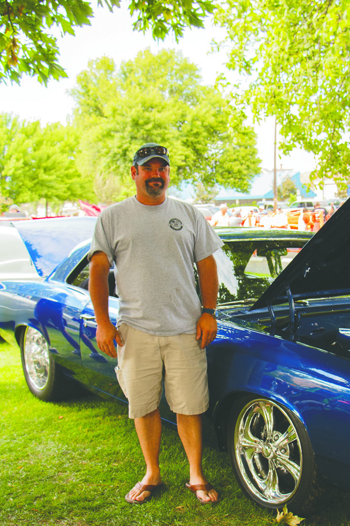 Jeff Berg stands next to the 1967 Chevy Chevelle that he and his father, Ron Berg, have worked on restoring.