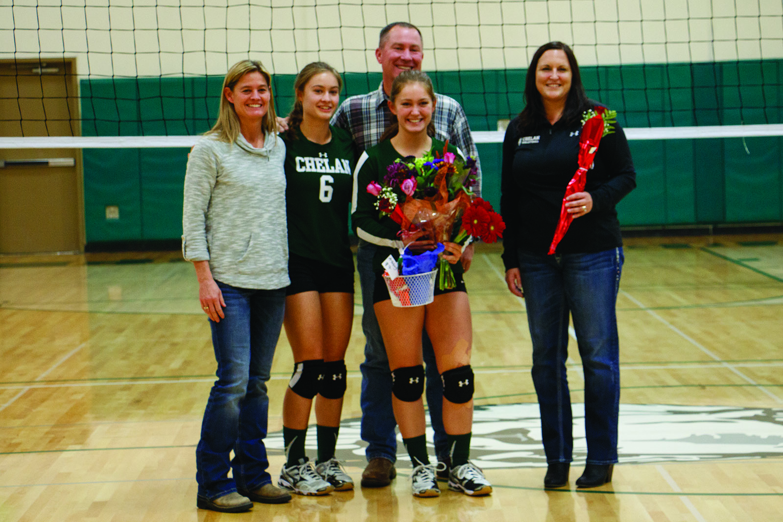 Ashley Oswald (center) stands with her parents, sister/teammate Molly Oswald, and Head Coach Jenifer Rainville (right), in celebration of Senior Night.
