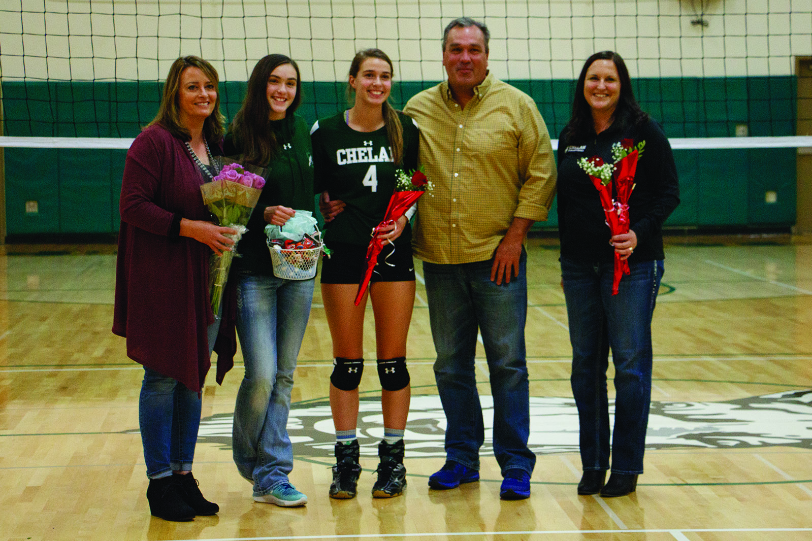 Sydney Hawkins stands with sister, parents, and Head Coach Jenifer Rainville.