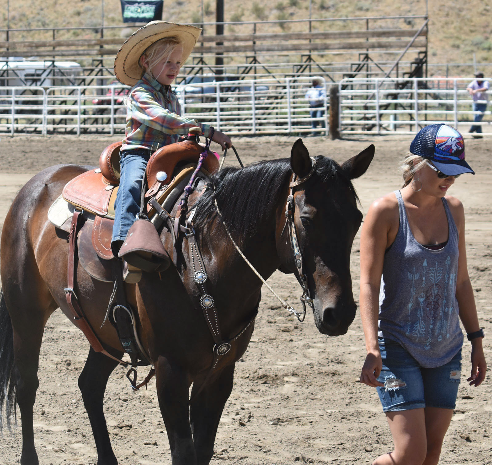 After pulling a ribbon from the tail of a goat, this cowgirl hopped back on her horse before being guided out of the arena.